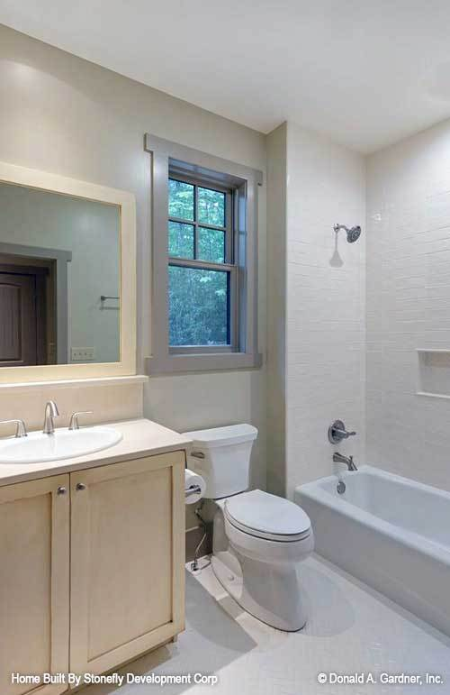 This bathroom has a light wood vanity, a toilet, and a shower and tub combo.