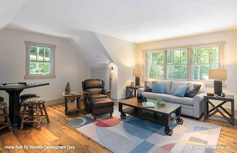 The bonus room is furnished with dark wood tables, a leather lounge chair, and cushioned stools, and a gray couch.
