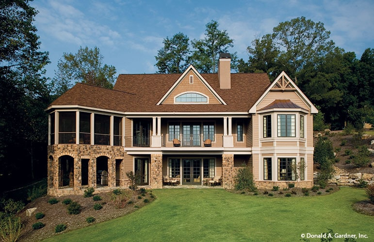 Rear exterior view with upper balcony and covered porches framed with stone brick columns.