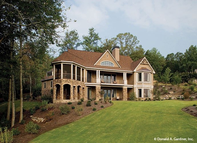 A farther view shows the gorgeous landscaping and well-maintained lawn surrounding the house.