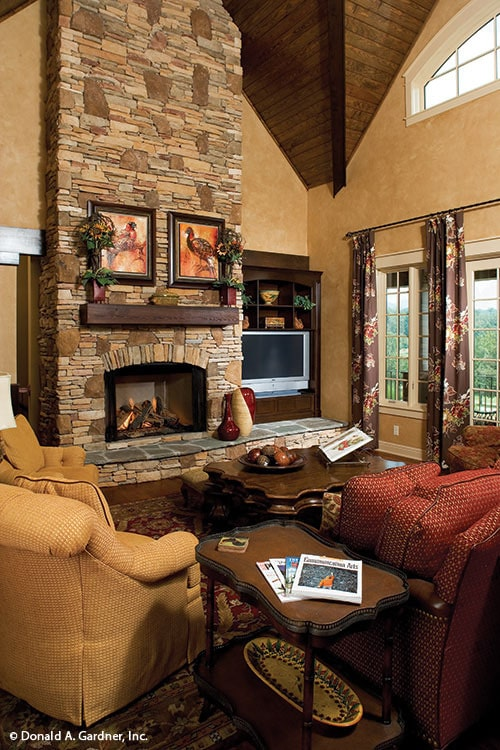Living room with a stone fireplace, cozy fabric seats, dark wood tables, and a flatscreen TV.