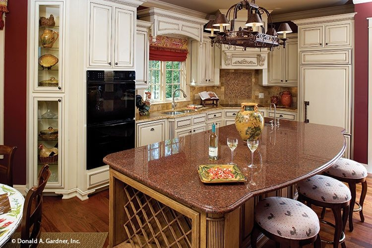 The kitchen is equipped with black appliances, a double bowl sink, and a metal pot rack hanging over the curve center island.