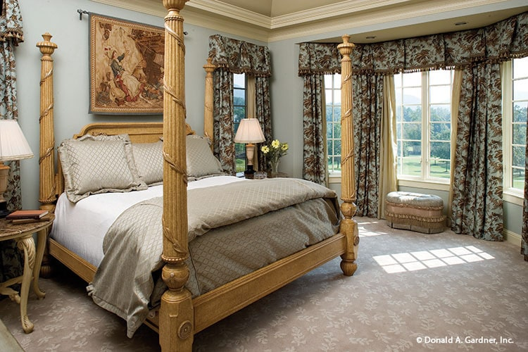 Primary bedroom with a four-poster bed, round nightstands, and a skirted ottoman sitting by the bay window