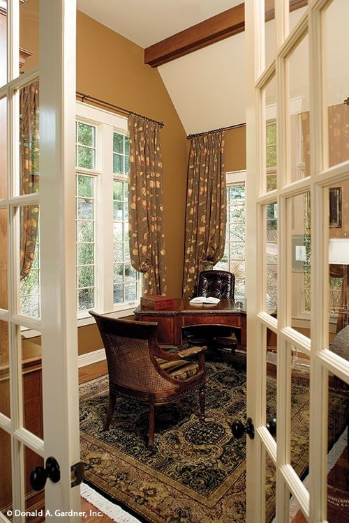 The study offers a dark wood desk, wooden armchair, and white framed windows dressed in gray floral drapes.