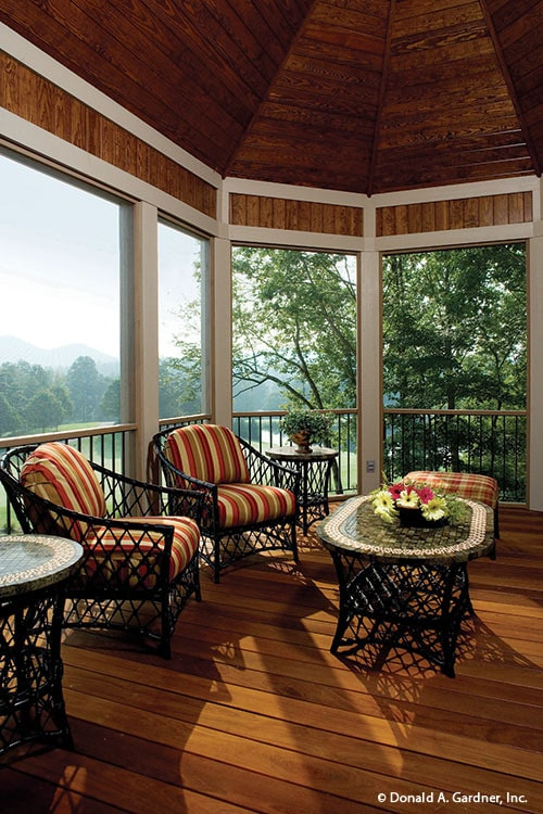 Wicker tables and matching chairs topped with red striped cushions fill the screened porch.
