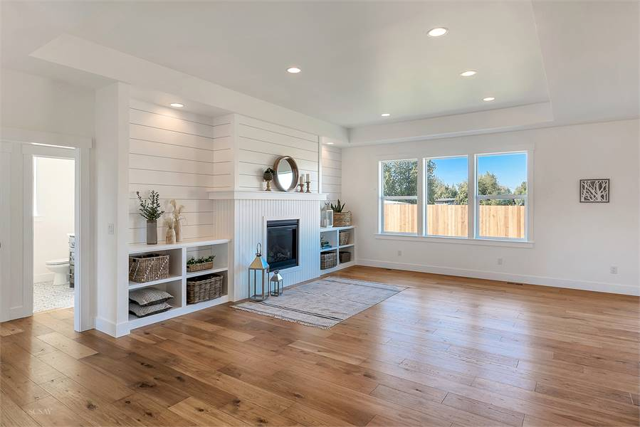 The living room has triple pane windows and a glass-enclosed fireplace flanked with white built-ins.