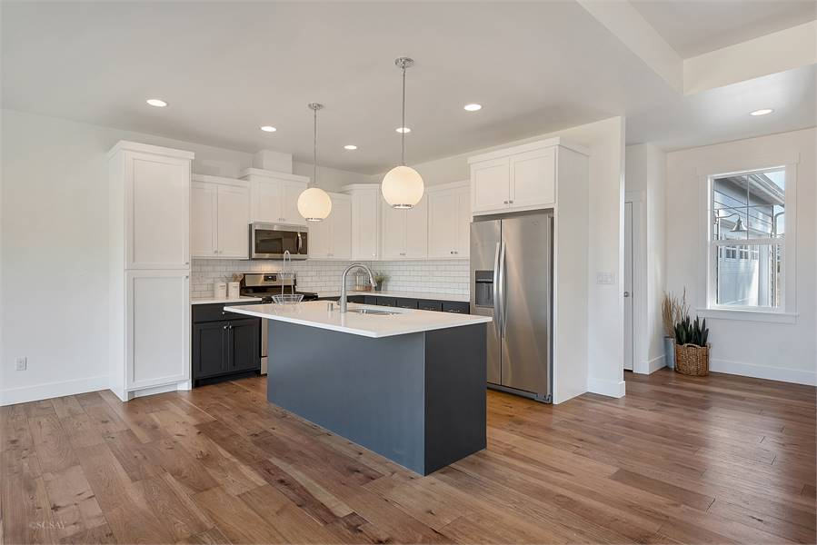 Kitchen with white and gray cabinets, subway tile backsplash, and a center island illuminated by glass globe pendants.