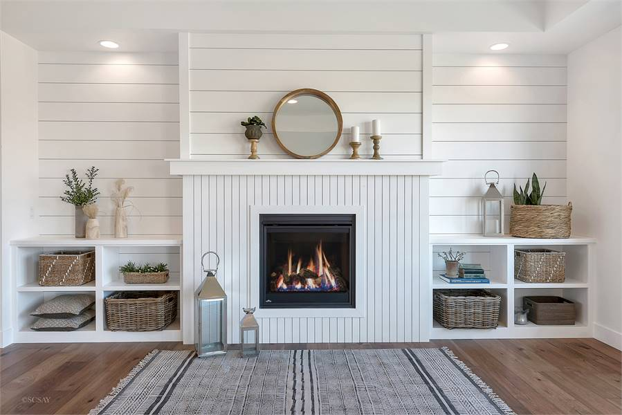 A closer look at the fireplace topped with a round mirror and candle holders.