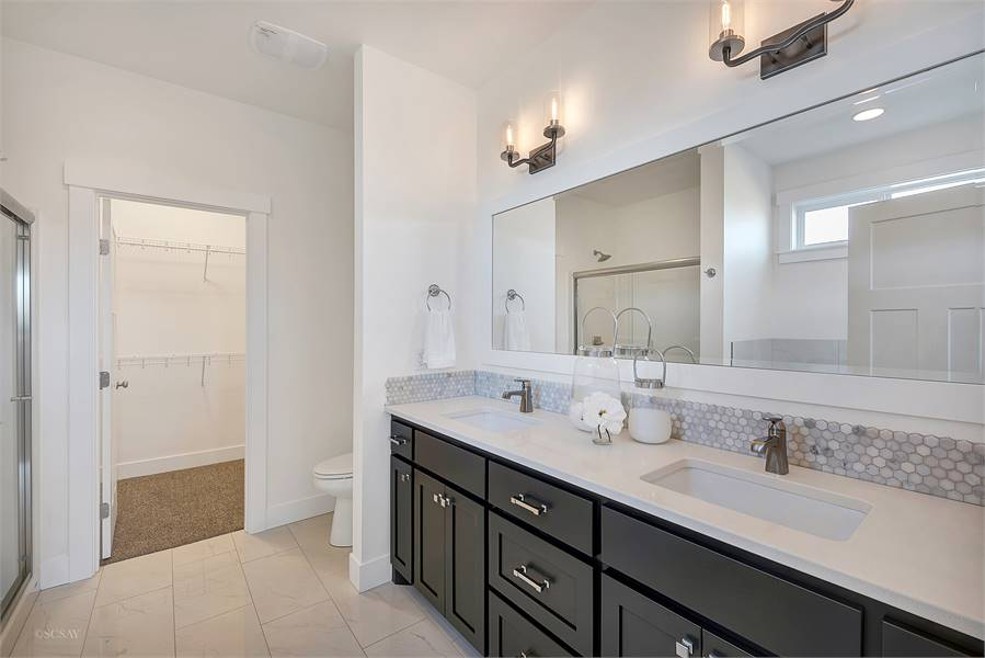 The primary bathroom has a walk-in closet, a toilet, dual sink vanity, and a shower area reflected in the rectangular mirror.