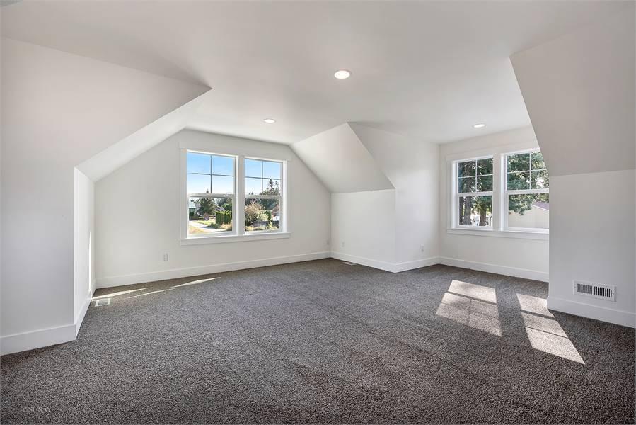 Bonus room with vaulted walls, white-framed windows, gray carpet flooring, and a regular ceiling.