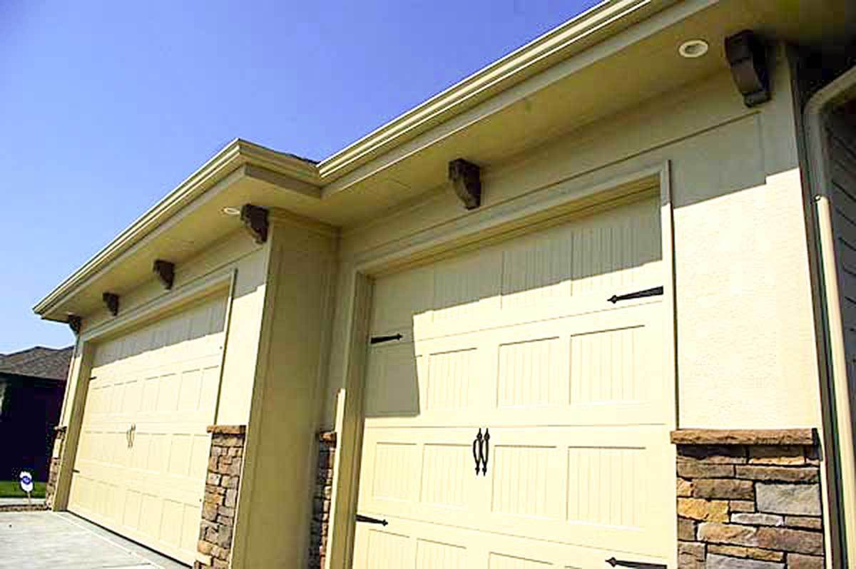 The three-car garage is adorned with brick accents and decorative wooden brackets.