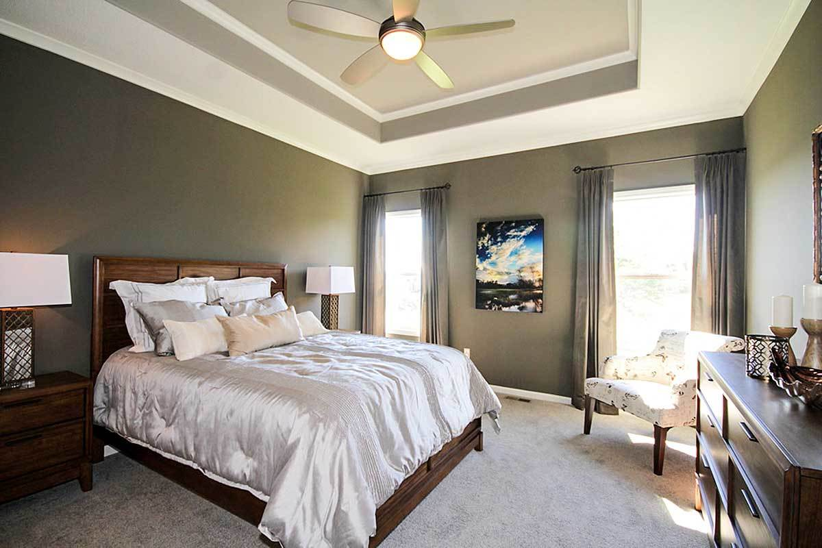Primary bedroom with dark wood furnishings, beige carpet flooring, and a striking tray ceiling mounted with a sleek ceiling fan.