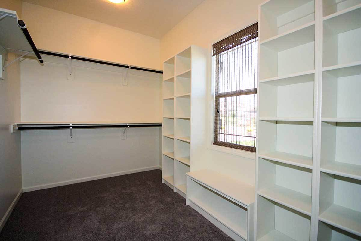 Walk-in closet with brown carpet flooring, white built-in shelves, and a glass window covered in a sheer wicker shade.