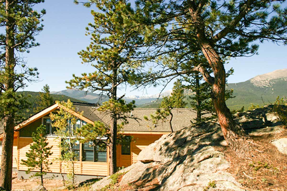 The house is surrounded by sloping lots and a stunning mountain backdrop.