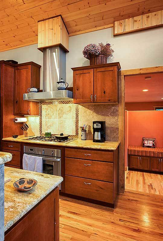 Stainless steel appliances and a sleek vent hood complete the kitchen.