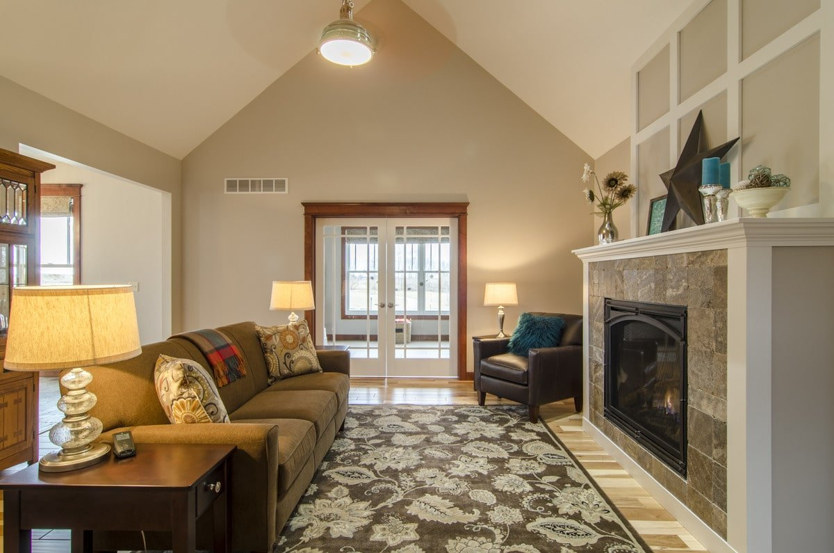 The living room offers a stone fireplace, brown sectional sofa, black leather armchair, and a floral area rug that lays on the light hardwood flooring.