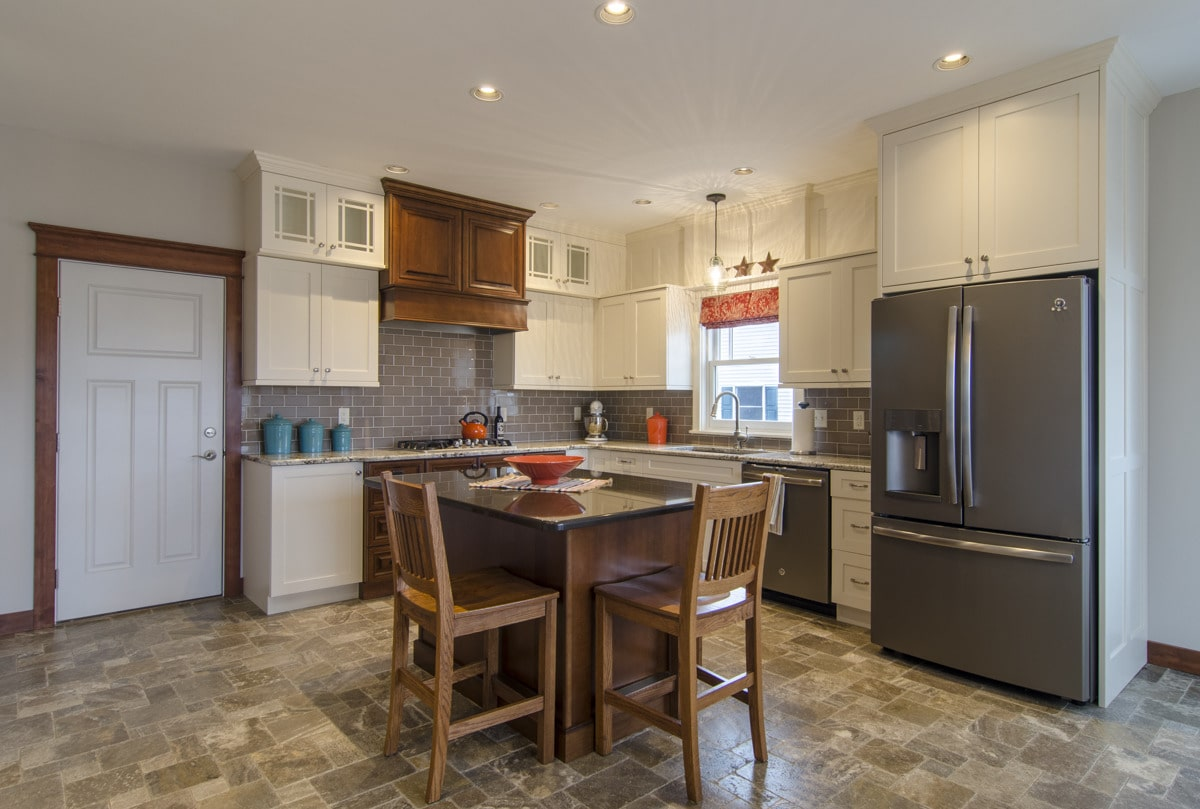 Kitchen with white cabinetry, slate appliances, gray subway tile backsplash, and a center island with two seating.