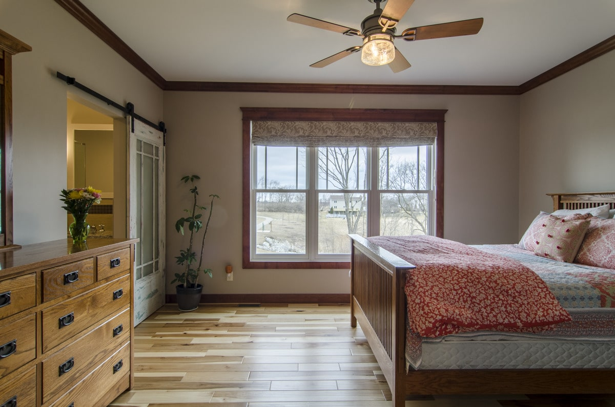 Primary bedroom with wooden furnishings, light beige wall, and a regular white ceiling lined with wooden crown moldings.