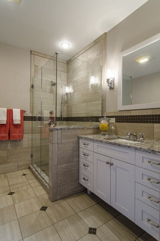 The primary bathroom is equipped with a walk-in shower and a white vanity topped with an undermount sink and granite countertop.