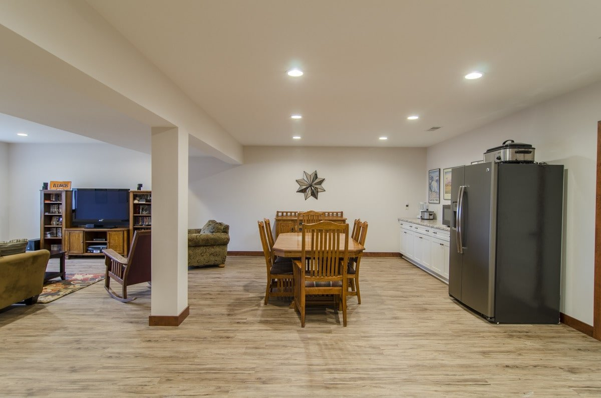The basement is filled with a wet bar, wooden dining set, and cozy seats surrounding the flatscreen TV.