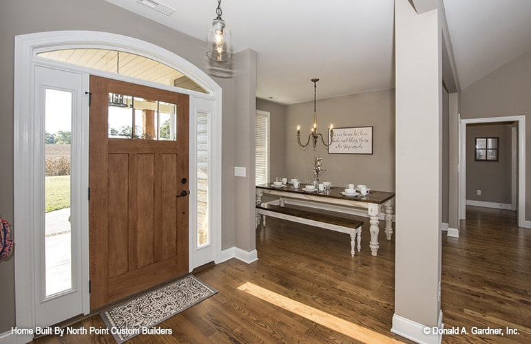 Foyer with a wooden entry door and a great view of the dining area defined with gray columns.