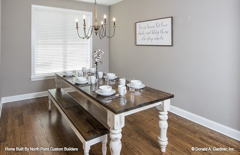 The dining room offers a candle chandelier and a wooden dining table paired with a matching bench.