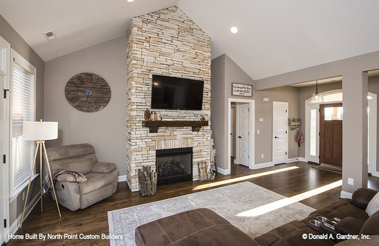 Living room with an L-shaped leather sofa, a velvet beige armchair, and a stone fireplace with a TV on top.