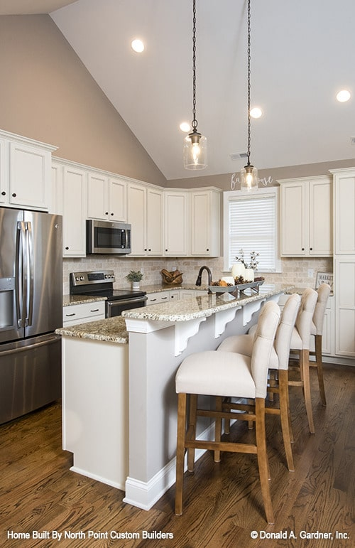 The kitchen is equipped with granite countertops, white cabinetry, stainless steel appliances, and a two-tier island bar.