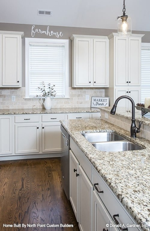 A closer look at the granite top island fitted with a double bowl sink and a wrought iron faucet.