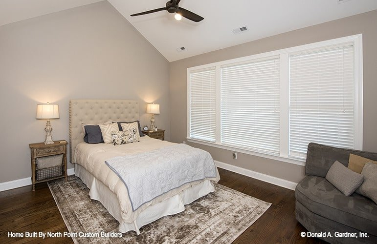 The primary bedroom is furnished with a gray cuddle chair, wooden nightstands, and a beige tufted bed sitting on a distressed area rug.
