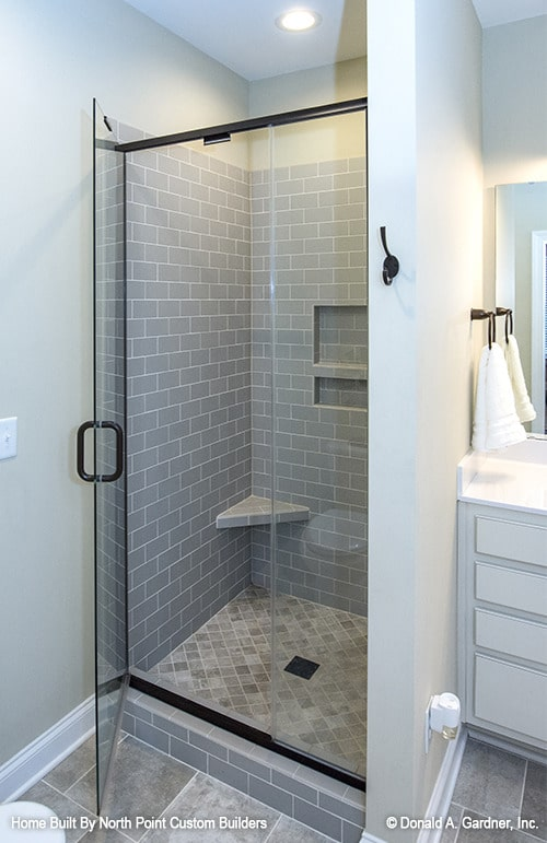 The walk-in shower features gray subway tile walls fitted with inset shelves and a corner tiled seat.
