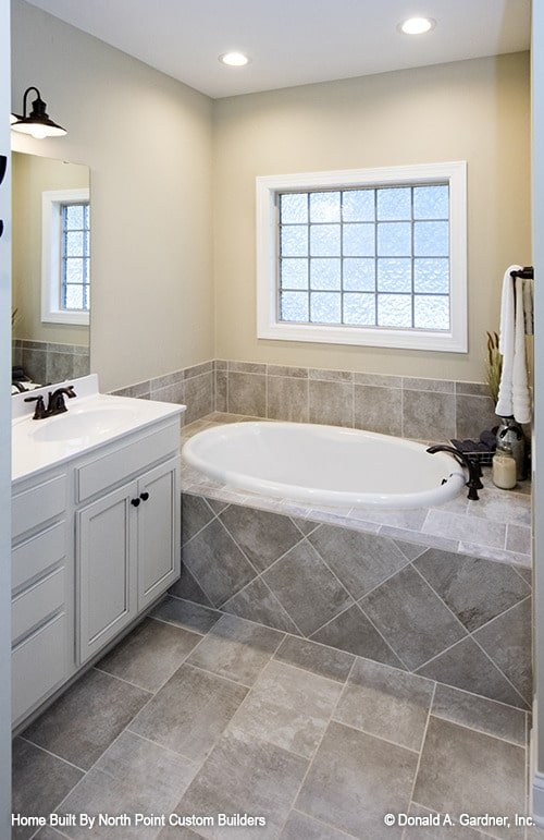 Primary bathroom with white sink vanity and a deep soaking tub fixed under the glass block window.