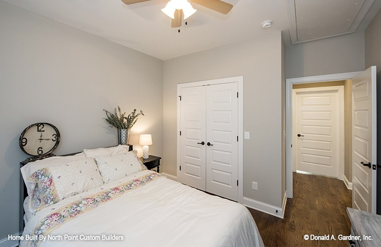 This bedroom has gray walls, hardwood flooring, and a comfy bed topped with a round clock and sleek vase.