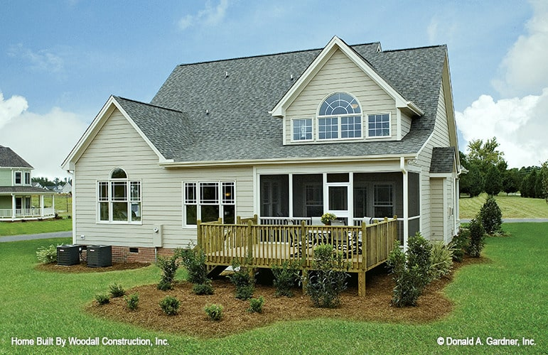Rear exterior view showing the screened porch and a spacious deck bordered by wooden railings.