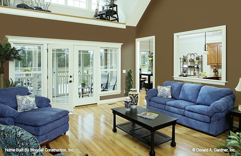 Living room with blue velvet seats, a black coffee table, and a french door that opens out to the back porch.