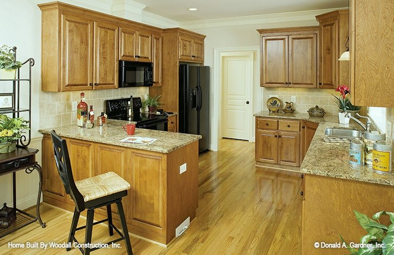 The kitchen is equipped with black appliances, granite countertops, wooden cabinetry, and a peninsula complemented with a cushioned chair.