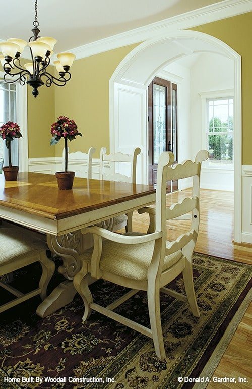 Formal dining room with a wooden dining set, an ornate chandelier, hardwood floor, and warm yellow walls adorned with white wainscoting and an open archway.