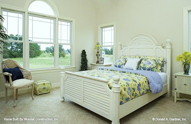 The primary bedroom has white furnishings, plush carpet flooring, and plenty of white-framed windows.
