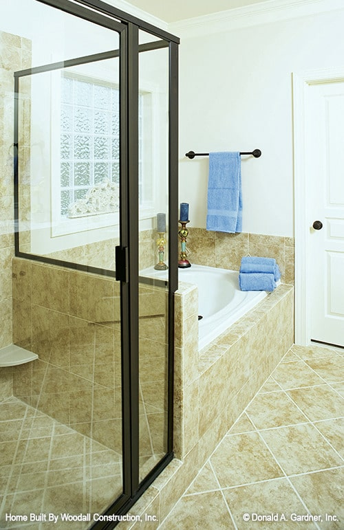 Primary bathroom with a walk-in shower and a deep soaking tub clad in beige marble tiles.