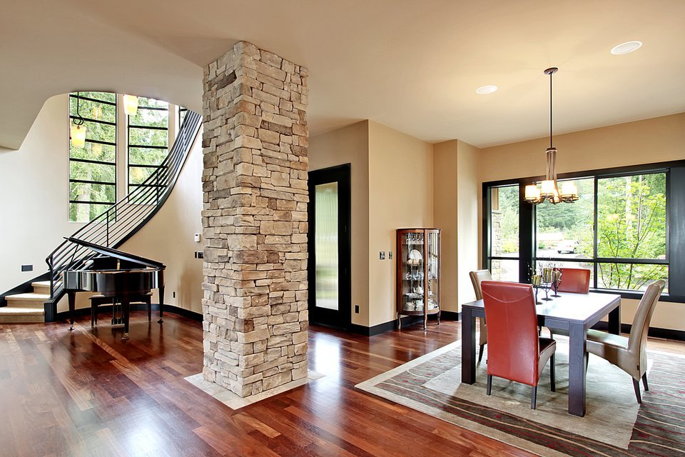 An open space showing the dining room and foyer with a curved staircase and a baby grand piano. The large stone pillar defines the dining room.