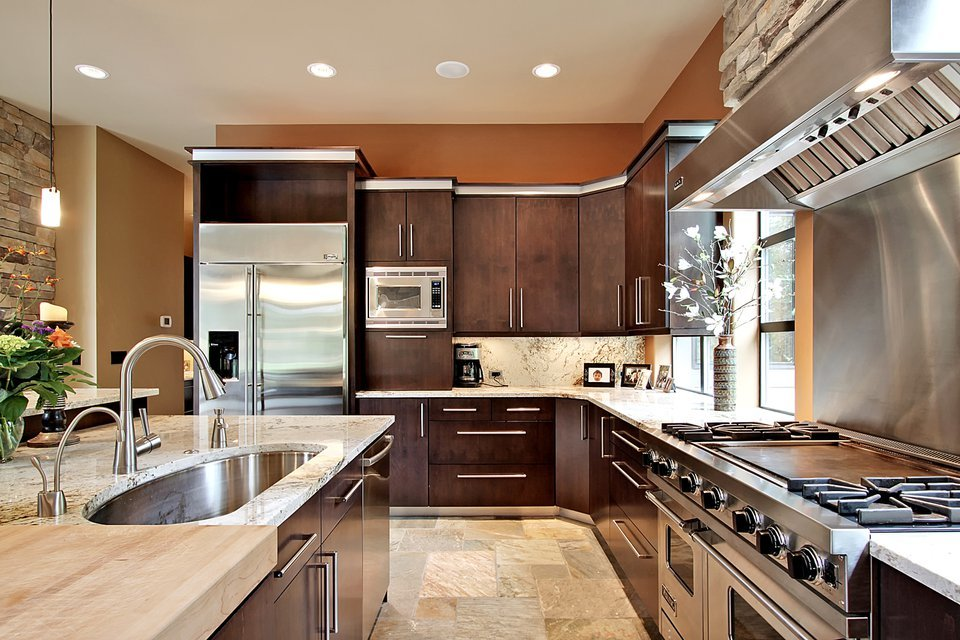 Kitchen with dark wood cabinetry, stainless steel appliances, and an undermount sink fitted on the immense island bar.