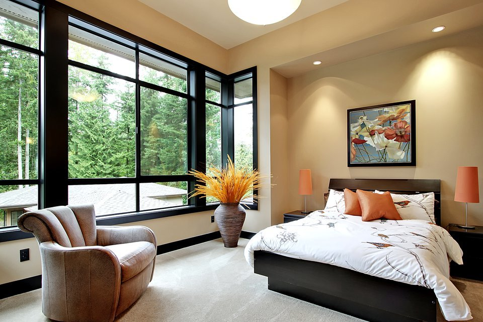 This bedroom has black aluminum framed windows, a stylish armchair, and a dark wood bed adorned with a floral painting.