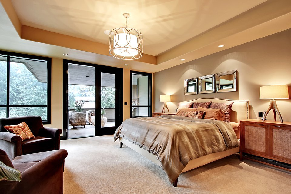 Primary bedroom with a tray ceiling, beige carpet flooring, and a french door that opens out to the private deck.