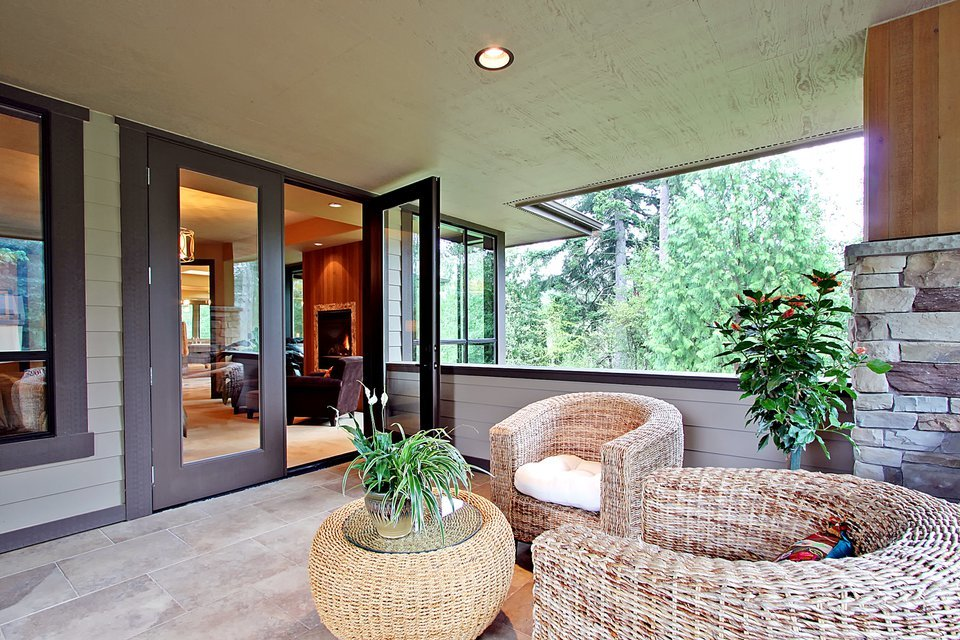 The private deck offers wicker round back chairs and a matching coffee table topped with a fresh potted plant.
