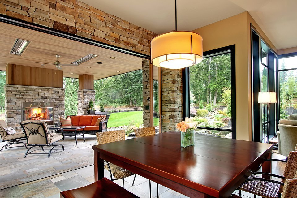 Breakfast nook overlooking the outdoor living with a stone fireplace and metal cushioned seats.