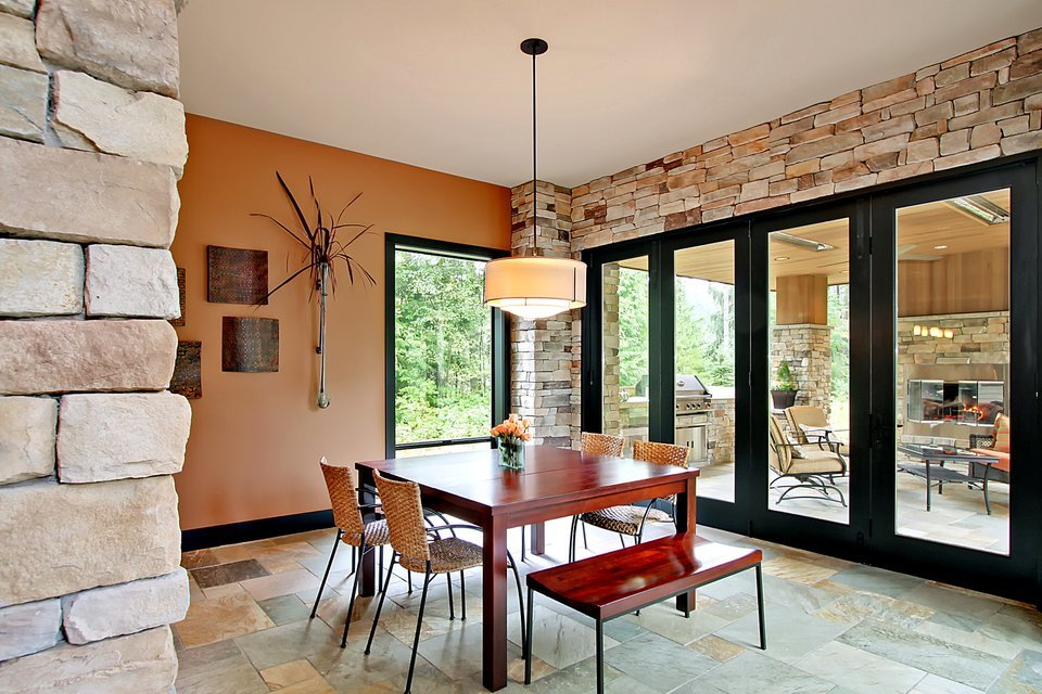 The breakfast nook offers wicker chairs, a redwood bench, and a matching dining table well-lit by a drum pendant light.