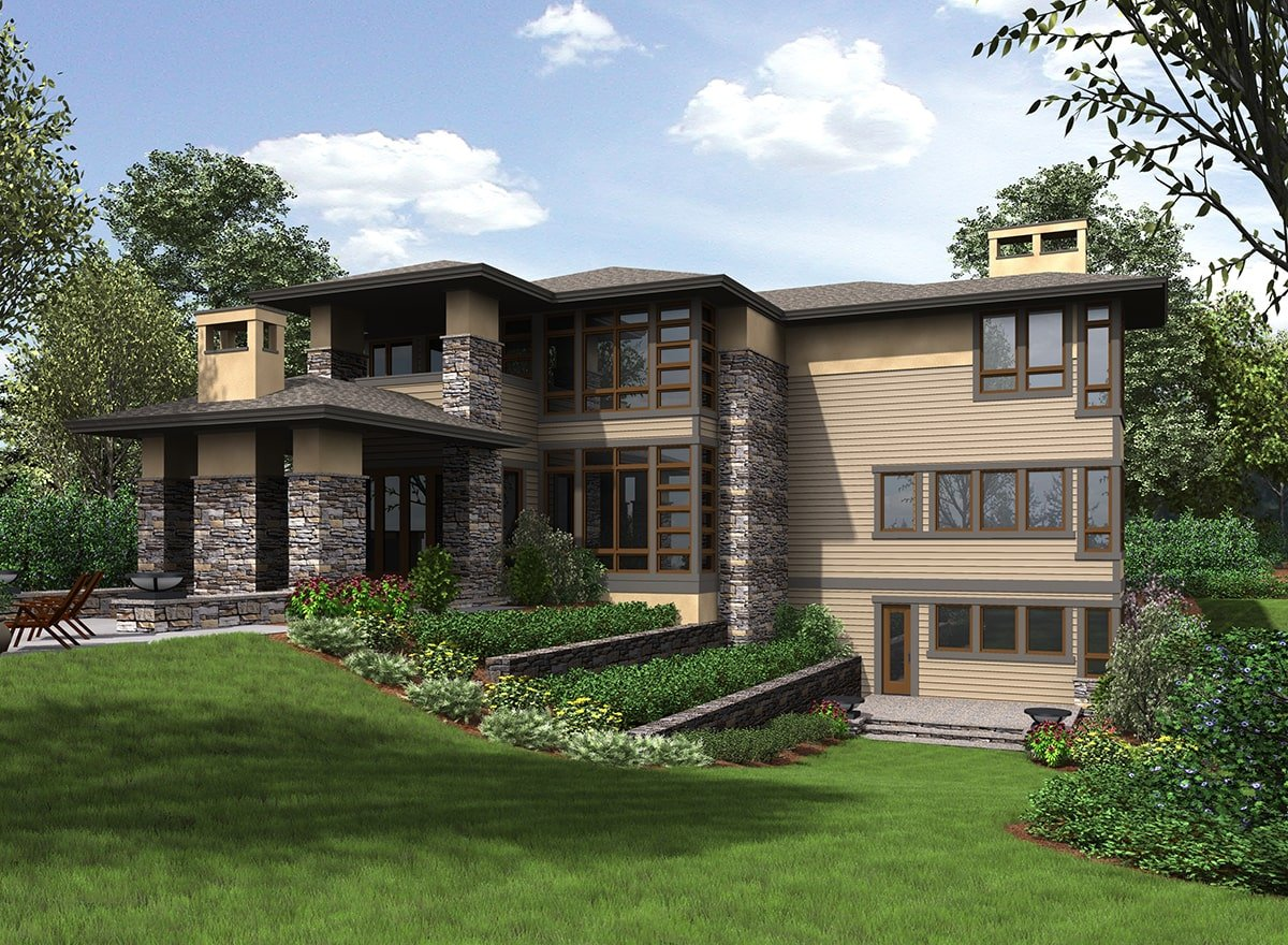 Rear exterior view showing the taupe siding, stone accents, and a lush green lawn surrounding the house.