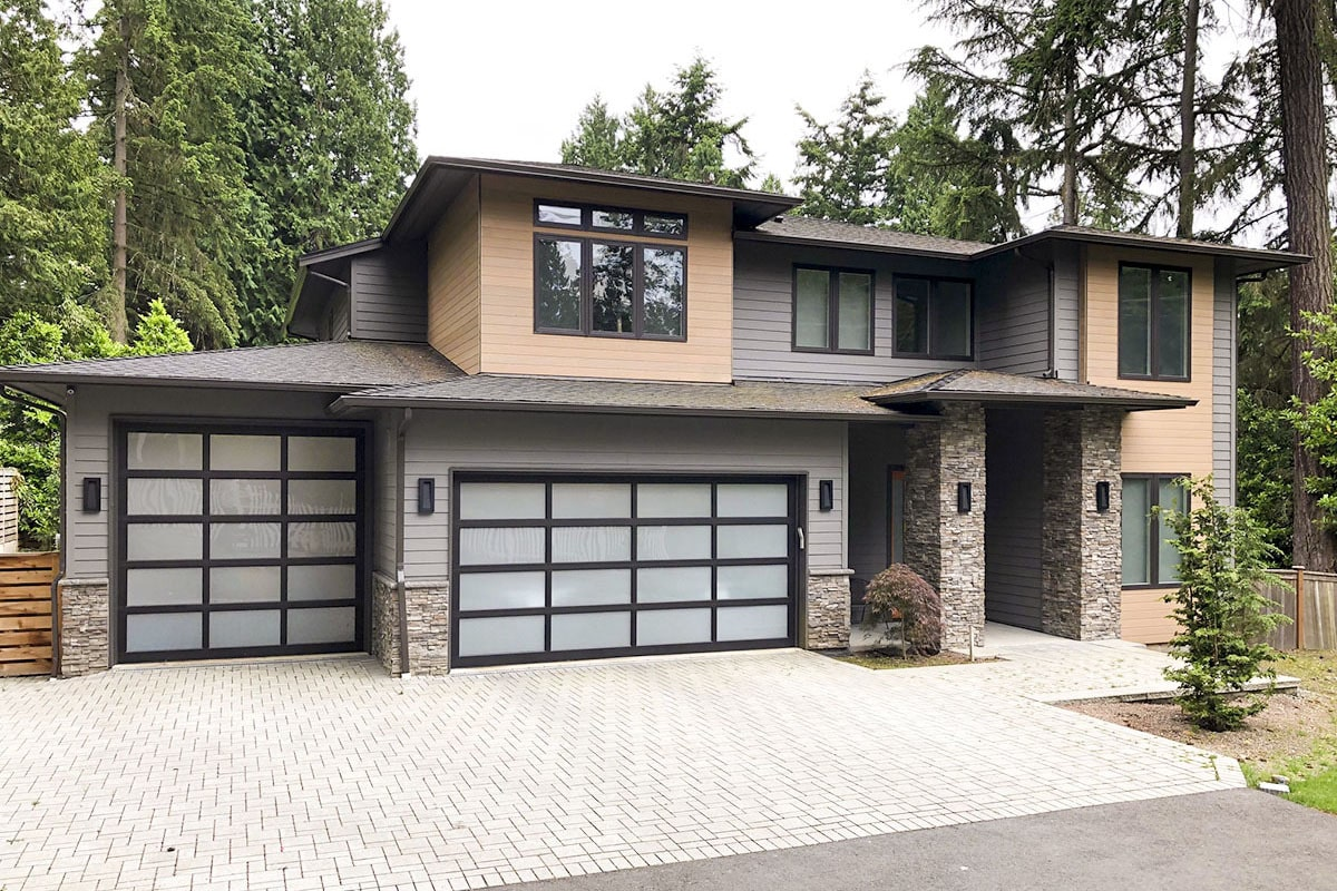 Home facade showcasing a gray and wooden exterior siding, stone accents, and a front entry garage enclosed in aluminum framed glass doors.