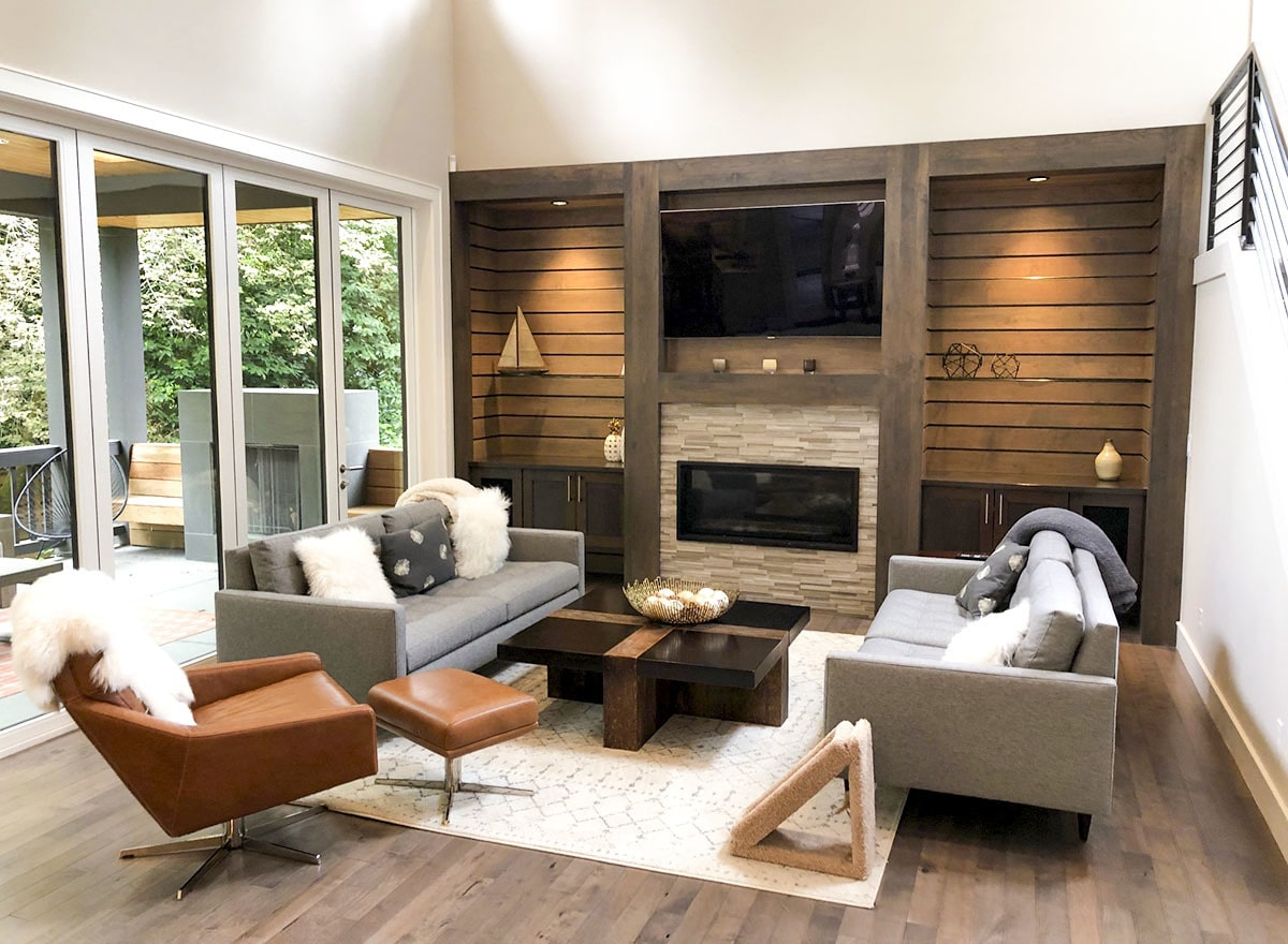 The living room has gray tufted sofas, a leather lounger chair, and a glass-enclosed fireplace with a wall-mounted TV on top.