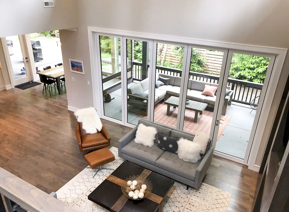 View of the living room from the second-floor balcony showing its natural hardwood flooring topped with a patterned area rug.